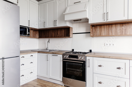 Luxury modern kitchen furniture in grey color and steel oven,fridge, sink, wooden tabletop. Gray cabinets in scandinavian style. Home renovation. Stylish kitchen interior design. © sonyachny
