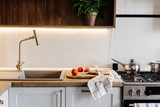Cooking food on modern kitchen with steel oven, pots, knife on wooden cutting board with vegetables  on wooden tabletop at sink with water. Home food. Stylish kitchen furniture in grey color - 242333141