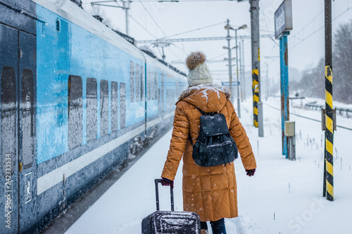 Woman with luggage is boarding to train on railroad station during snowing