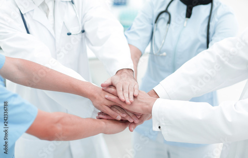 doctors holding hands together at hospital