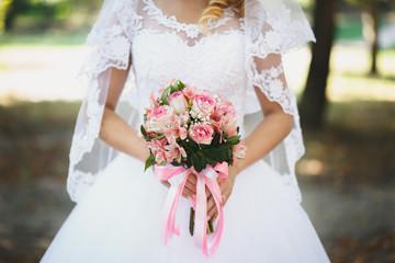 Beautiful bride holding wedding bouquet