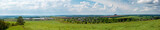 Panorama of green fields and forests