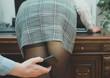 Leinwandbild Motiv Sexual harassment at work. Man taking a photo with mobile phone of secretary's butt.
