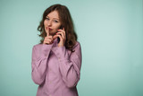 Young attractive woman holding mobile phone and showing silence gesture isolated on a background - 242343387