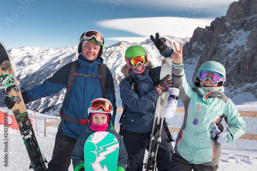 Leinwanddruck Bild Happy family skiing at the mountains. Kids in ski school.