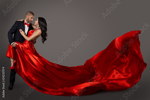 Leinwandbild Motiv Dancing Couple, Woman in Red Dress and Elegant Man in Suit, Flying Waving Fabric