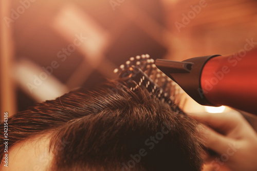 Man makes styling with hair dryer. Care and style concept