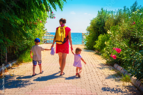 Family on summer rest. Mother and children go to sea beach
