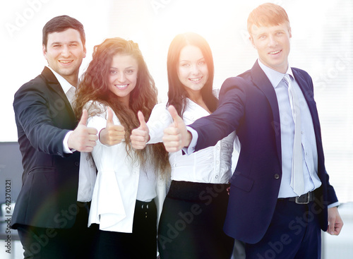 triumphant business team holding thumbs up © FotolEdhar