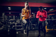 Fit beautiful focused girl warming up in a gym with her personal trainer by her side.