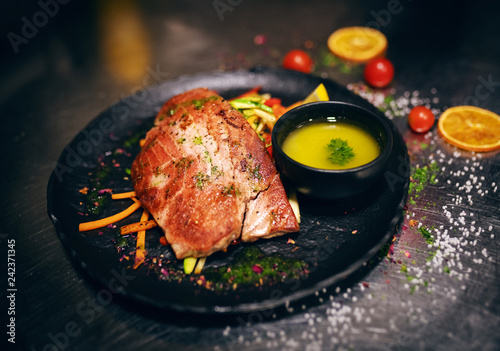 Foto Murales Close up of delicious tuna steak on crunchy vegetables. On plate little bowl of soup, too.