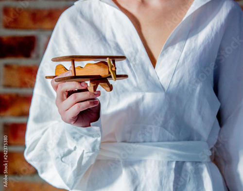 Woman in white shirt holding a wooden toy airplane. Concept of springtime travel