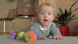 Slow motion shot of eight months baby girl lying on the floor at home and changing her emotions from surprise to happiness - 242379742