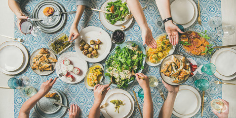 Mediterranean style dinner. Flat-lay of table with salads, starters, pastries over blue table cloth with hands holding drinks, sharing food, top view. Holiday gathering, vegetarian party concept