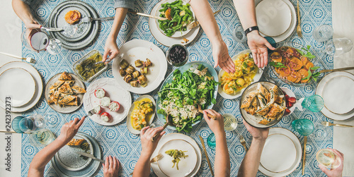 Leinwandbild Motiv Mediterranean style dinner. Flat-lay of table with salads, starters, pastries over blue table cloth with hands holding drinks, sharing food, top view. Holiday gathering, vegetarian party concept