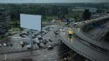 Timelapse shot of car traffic on multilevel crossing. City view with hotel, parking lot and blank banner on rainy day - 242395759