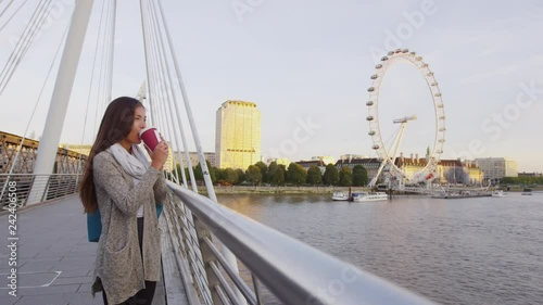 London woman drinking coffee on bridge over the Thames. Young female professional business woman in London, England. Beautiful young multiracial Asian Caucasian girl.
