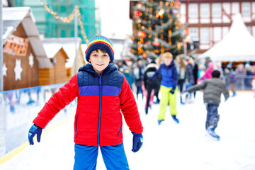 Happy little kid boy in colorful warm clothes skating on a rink of Christmas market or fair. Healthy child having fun on ice skate. Lot of people celebrating holiday and having active winter leisure