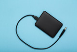 Black external hard disk with USB cable on blue background. Top view. - 242418780