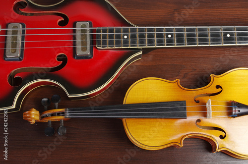 Bass guitar and violin on a wooden table - 242422163