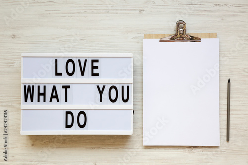 Foto Murales Modern board with text 'Love what you do', pencil and noticepad over white wooden background, top view. Business concept. From above, flat-lay, overhead.