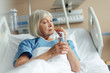 selective focus of senior woman lying in bed, holding glass of water and taking pill in hospital