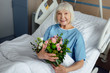 Leinwanddruck Bild - happy recovering senior woman lying in bed with flowers and looking at camera in hospital