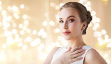 jewelry, luxury and people concept - portrait of woman in white dress with diamond earring and finger ring over beige background and festive lights