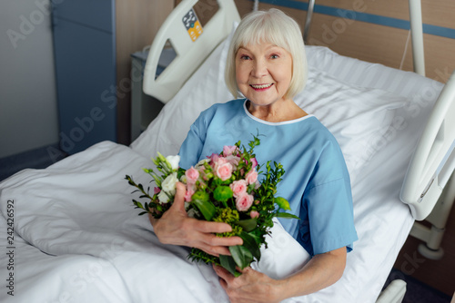 Leinwanddruck Bild happy recovering senior woman lying in bed with flowers and looking at camera in hospital