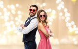 valentines day, love and people concept - happy couple in heart-shaped sunglasses over beige background with festive lights - 242428310