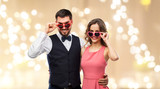 valentines day, love and people concept - happy couple in heart-shaped sunglasses over festive lights background - 242428381