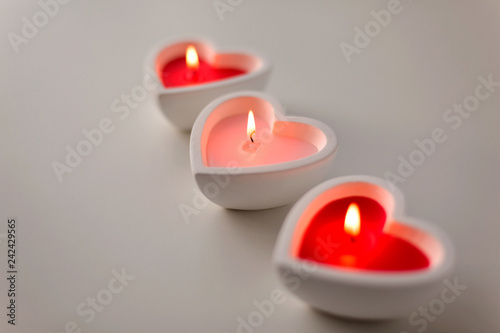 valentines day and decoration concept - heart shaped candles burning © Syda Productions