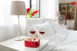 valentines day, love and romantic concept - heart shaped gift box and two glasses of red wine on bedroom nightstand at home