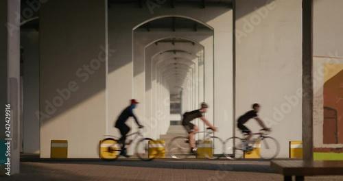 4K Riders on Bikes Under Symmetrical Bridge