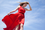 Blonde in red dress standing against a blue sky - 242431598