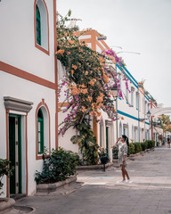 Puerto de Mogan Gran Canaria, colorful harbor village Gran Canaria, men walking at the old Streets with flowers on the walls
