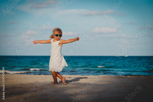 obraz lub plakat cute little girl dance play at summer beach