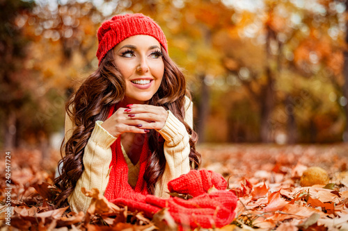 Young woman lying on the autumn leaves in the park