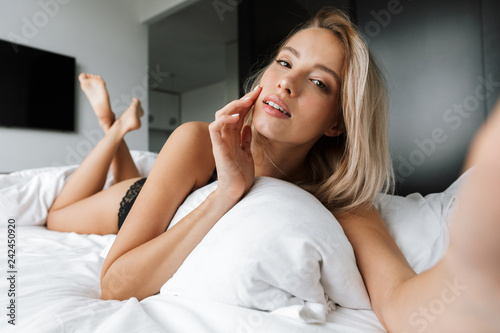 Leinwandbild Motiv Beautiful smiling young woman wearing lingerie laying