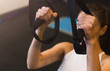 Girl holding strap during suspension training in the gym