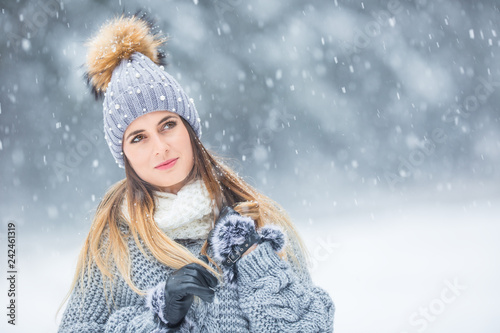 Portrait of young beautiful woman in winter clothes and strong snowing.