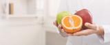 Unrecognizable nutritionist holding fresh fruit, copy space