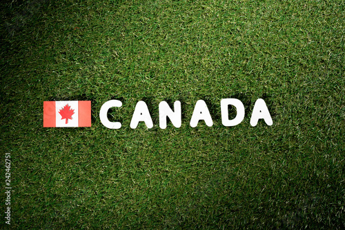 top view of word 'Canada' with canadian flag on green grass background