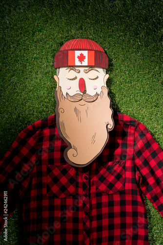 cardboard man in plaid shirt and hat with maple leaf on green grass background