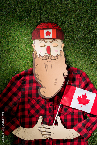 cardboard man in plaid shirt and hat with maple leaf holding canadian flag on green grass background