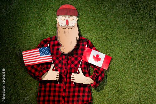 cardboard man in plaid shirt and hat holding canadian and american flags on green grass background