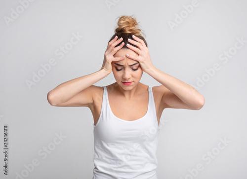 Leinwanddruck Bild Exhausted woman suffering from unbearable headache over background