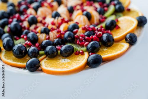 Foto Murales Fruit dessert. Orange, grapes, pomegranate on a white plate. Festive table.