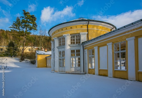 Yellow and white building of Ferdinand colonnade with mineral water at spa town Marienbad, Czech Republic, snowy winter scene in park, sunny day, blue sky with clouds, green pine tree