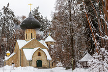 "Постер, картина, фотообои ""An old secret Orthodox church built in 1908 in a winter forest. Mysterious forest temple with a large copper dome. An unusual temple for prayer in the winter forest next to the gazebo."""